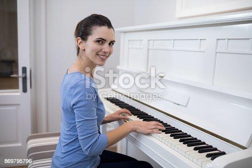 istock Portrait beautiful woman playing piano 869795796