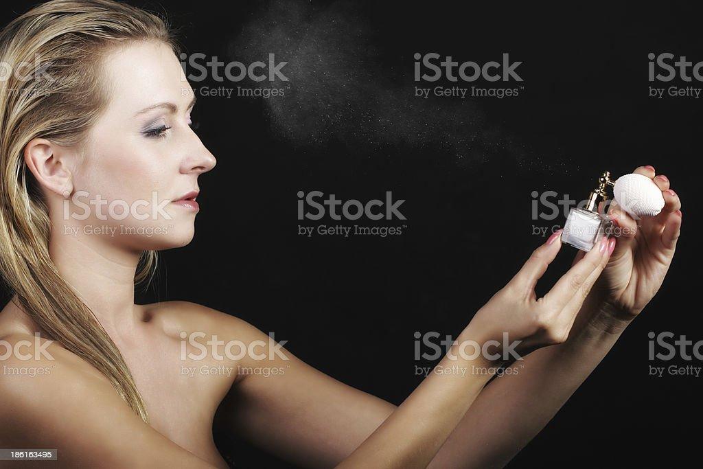 portrait beautiful woman spraying perfume on black royalty-free stock photo