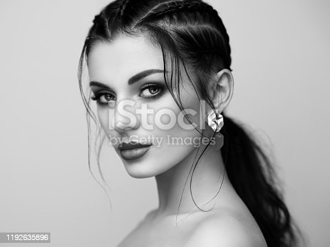 Brunette girl with perfect makeup. Beautiful model woman with curly hairstyle. Care and beauty hair products. Lady with braided hair. Model with jewelry. Black and white photo