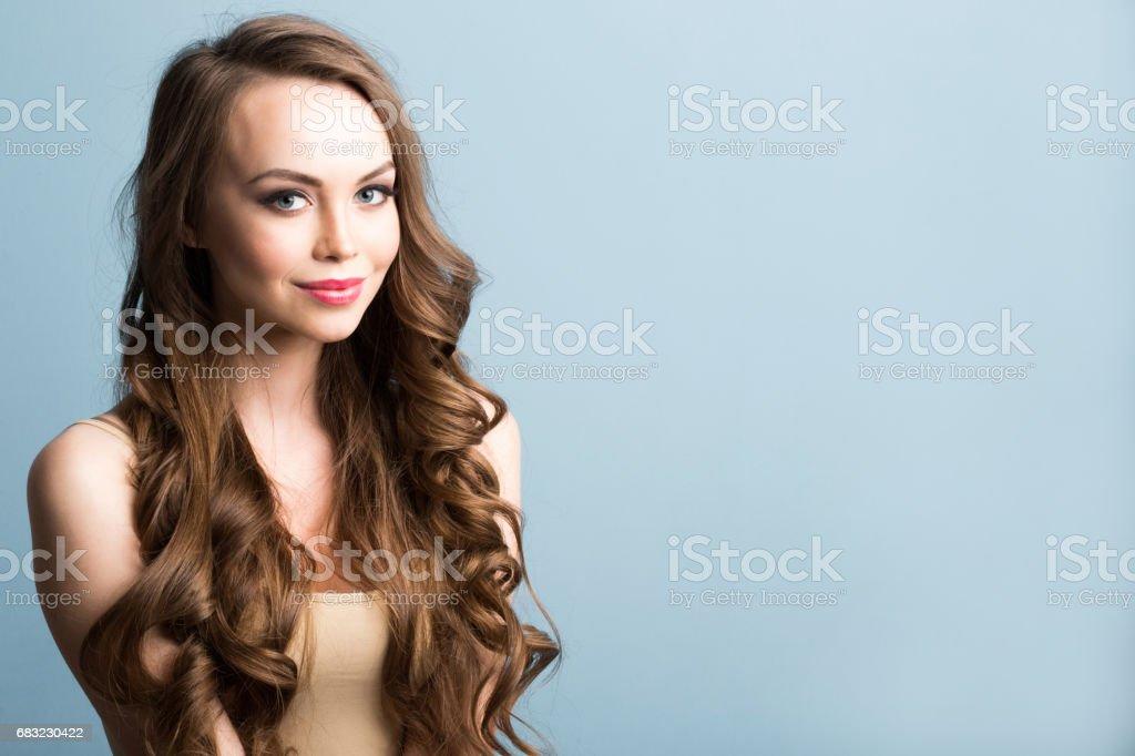肖像與長長的卷髮的漂亮的女人。 免版稅 stock photo