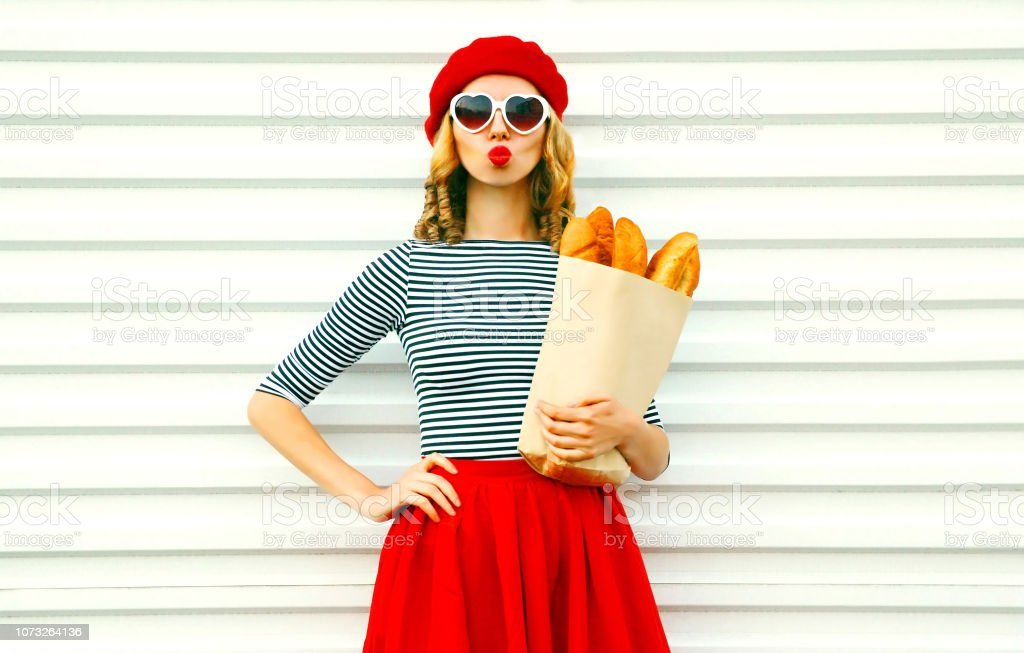 Portrait beautiful young woman blowing lips making air kiss wearing red beret holding in hands paper bag with long white bread baguette on white wall background stock photo