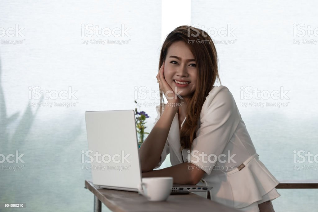 Portrait beautiful young woman who is an Asian businessman smiling happy working with a laptop in a coffee shop Cafe. royalty-free stock photo