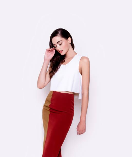 porträt schöne junge frau mit glänzendem make-up trägt weißes top und zwei farbigen rock beauty cosmetics healthcare konzept - rote bleistiftröcke stock-fotos und bilder