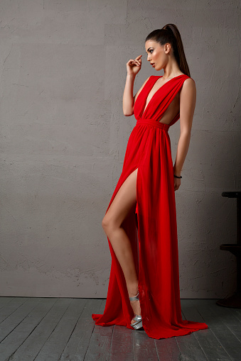Beauty, fashion portrait. Original looks. Beautiful and fresh young  woman, dressed elegantly.  Wearing a red dress. Brown hair, hair ponytail. Gray wall background. Developed from RAW, Adobe RGB color profile.