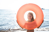 A beautiful girl goes swimming in the sea with floating ring and looking through it