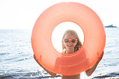 Girl looking through inflatable ring at the beach