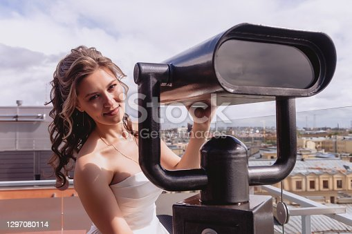 Portrait bride on observation deck stand on roof with panoramic view of old town. Pretty woman in wedding dresses on Sunny wedding day. Female in amazing view. Happy bride on background of city