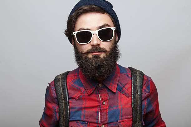 Portrait brutal bearded hipster man Portrait brutal bearded hipster man over grey background. Young man face closeup wearing a hat and backpack. lumberjack stock pictures, royalty-free photos & images