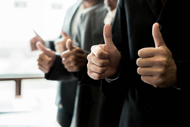 portrait business people giving thumbs up in meeting room, business concept, teamwork concept - convalida foto e immagini stock