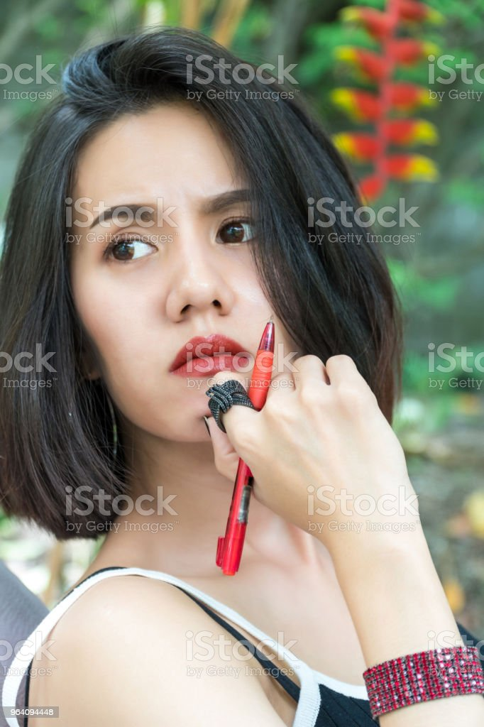 Portrait cheerful beautiful woman:Attractive woman has nice smile. She holds a pen and is thinking. Charming girl has beautiful face and nice skin. - Royalty-free Adult Stock Photo