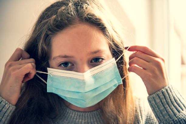 Portrait close up of girl wearing protective mask during pandemic