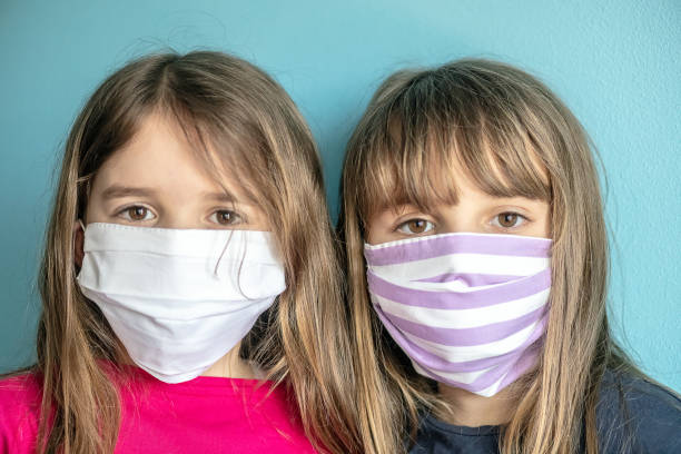 Portrait close up of little girls sisters children wearing protective mask during pandemic stock photo