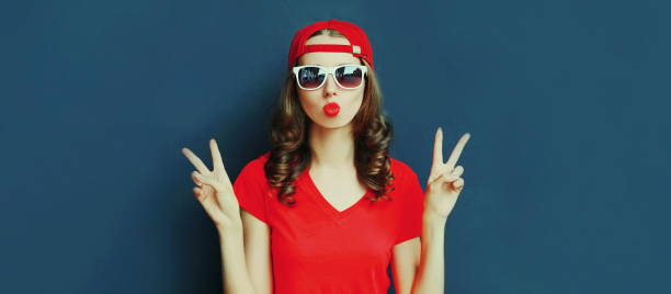 Portrait close up of young woman showing peace sign gesture wearing baseball cap over blue background stock photo