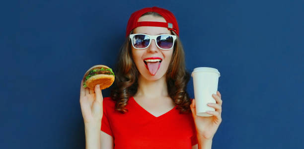 Portrait close up of young woman with burger and coffee cup wearing baseball cap, sunglasses over blue background stock photo