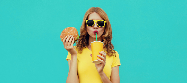 Portrait close up of young woman with fast food, burger and cup of juice wearing a yellow t-shirt, sunglasses on a blue background
