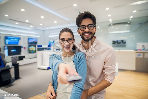 istock Portrait close up view of attractive happy excited hipster young love romantic couple standing hugged while girl pointing with the remote controller at the camera in a tech store. 941205484