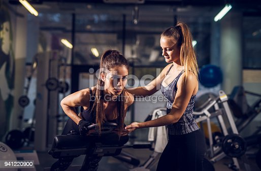 istock Portrait close up view of young smiling attractive healthy fitness sporty active slim girl doing low back exercise on the machine with weight while her pretty female personal trainer standing next to her and assisting in the gym. 941220900