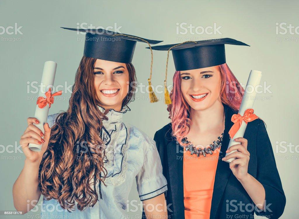 Closeup Portrait schöne glückliche Absolventen, zwei abgestuften Student Mädchen, junge Frauen in GAP Kleid drehen lächelnd hält Diplom Scroll isoliert grünen Hintergrund Wand. Abschlussfeier feiern – Foto
