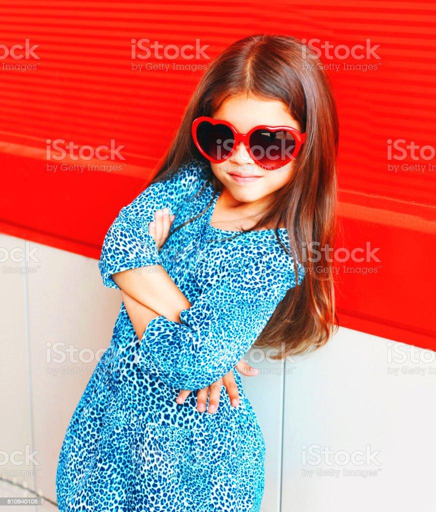 Closeup retrato lindo vestido de criança menina em óculos de sol vermelhos  e o leopardo foto 3e7bb3f18e