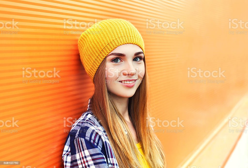Portrait closeup beautiful young girl in yellow hat over colorful