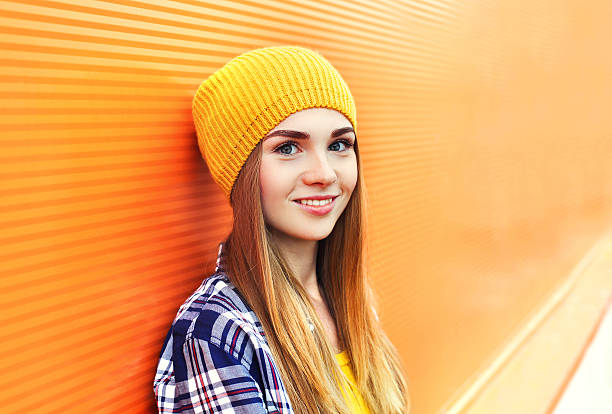Portrait closeup beautiful young girl in yellow hat over colorful stock photo
