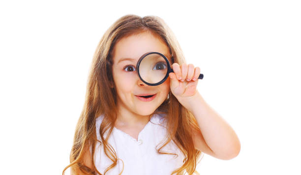 Portrait close-up little girl child looking through magnifying glass isolated on white background stock photo