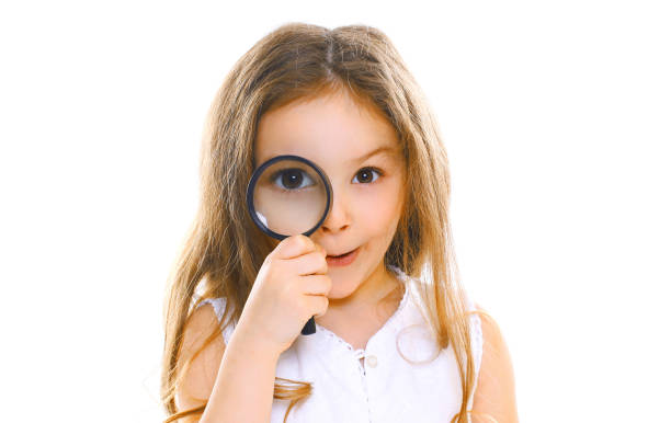 Porträt aus der Nähe kleine Mädchen Kind Blick durch die Lupe isoliert auf weißem Hintergrund – Foto