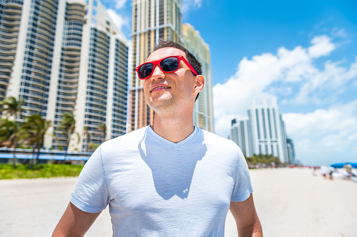 Portrait closeup of young man hipster millennial on beach with red sunglasses in Miami, Florida by apartment condo building in blurry background in summer