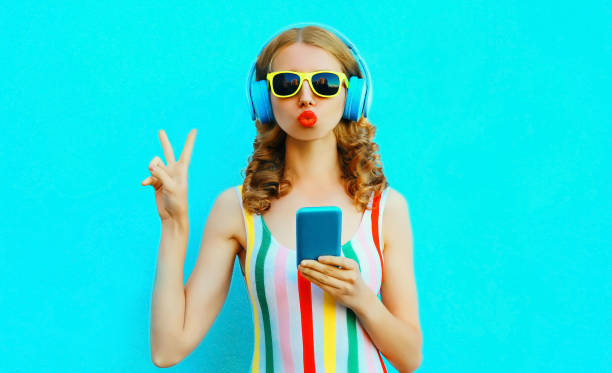 Portrait cool girl blowing red lips sending sweet air kiss holding phone listening to music in wireless headphones on colorful blue background stock photo