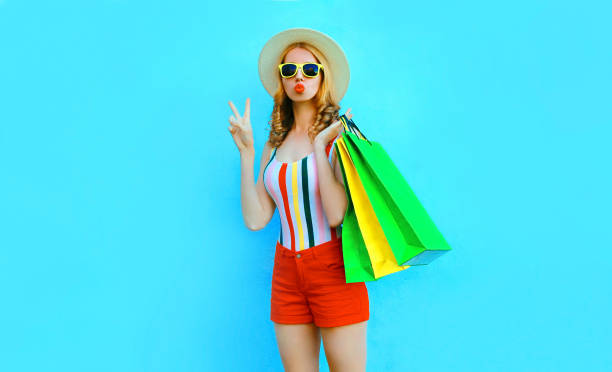 Portrait cool girl blowing red lips sends air kiss posing with shopping bags in colorful t-shirt, summer straw hat on blue background stock photo