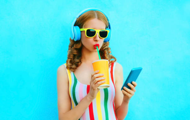 Portrait cool girl drinking fruit juice holding phone listening to music in wireless headphones on colorful blue background stock photo