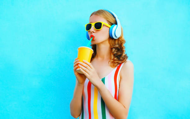 Portrait cool girl drinking fruit juice listening to music in wireless headphones on colorful blue background stock photo
