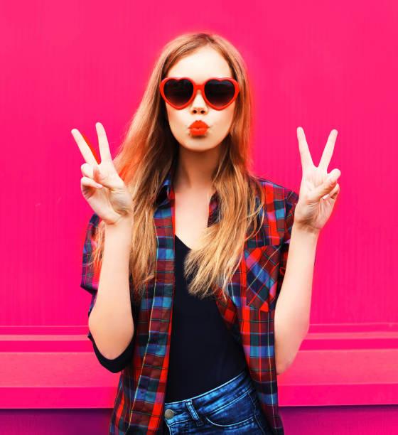 Porträt coole Mädchen in herzförmigen Sonnenbrille senden süßen Luft Kuss auf bunten rosa Hintergrund – Foto