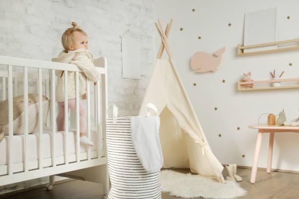 porträt niedliche baby mädchen steht in der krippe in ihrem kinderzimmer - tipi bett stock-fotos und bilder