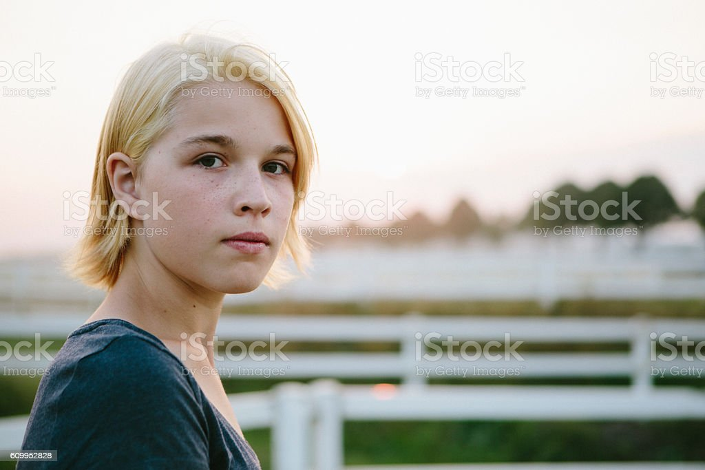 portrait: cute blonde teenager girl looks seriously at the camera stock photo