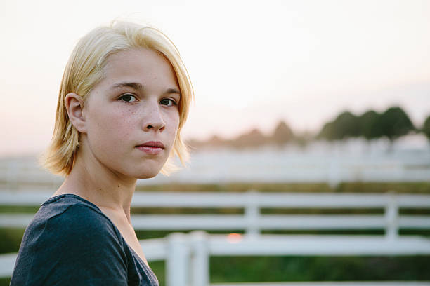 portrait: cute blonde teenager girl looks seriously at the camera  Cute blonde teenager girl outdoors, looking at camera, sunset 14 15 years stock pictures, royalty-free photos & images