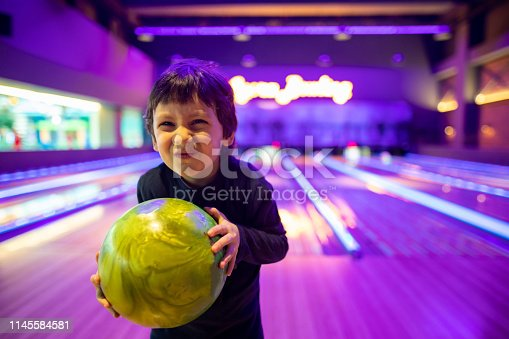 Portrait Cute child with ball in bowling club