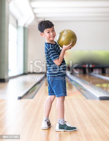 istock Portrait Cute child with ball in bowling club 984107582