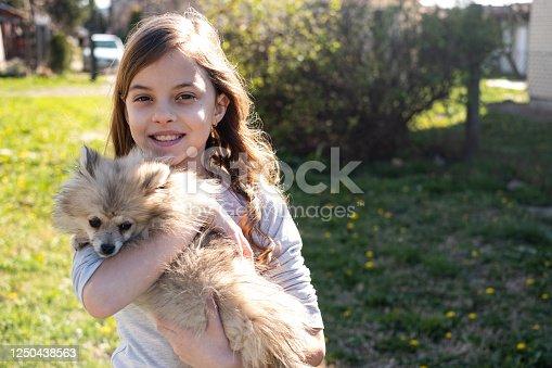 Cute girl holding small dog at backyard
