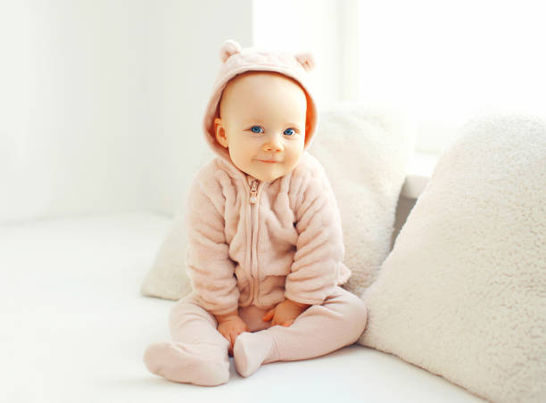 Portrait cute smiling baby sitting in white room at home near window stock photo