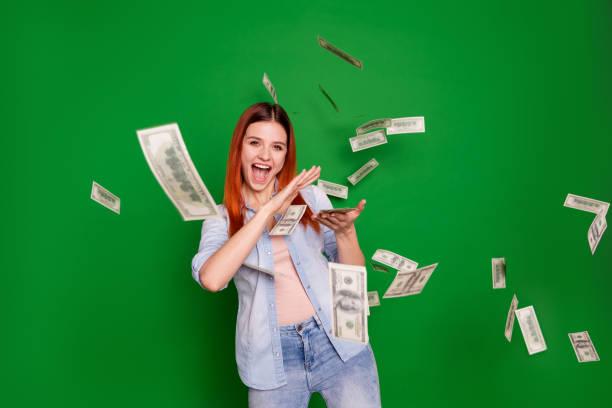 retrato encantado dama extática de la mano obtener salarios salario rico objetivo contento satisfecho positivo feliz contenido hermoso de moda jeans de vestir de estilo largo recto aislado en fondo verde - bota fotografías e imágenes de stock