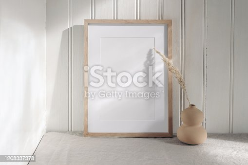 Portrait empty wooden frame mockup with modern ceramic vase, dry grass in sunlight, long shadows. White beadboard wainscot wall paneling background, Scandinavian interior, home design. Art concept.