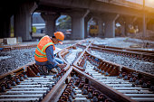 istock Portrait engineer under inspection and checking construction process railway switch and checking work on railroad station .Engineer wearing safety uniform and safety helmet in work. 1269800276