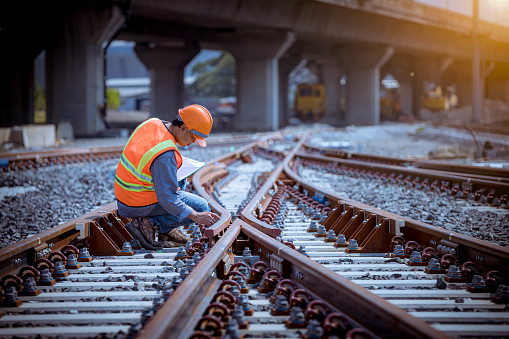 Portrait engineer under inspection and checking construction process railway switch and checking work on railroad station .Engineer wearing safety uniform and safety helmet in work.