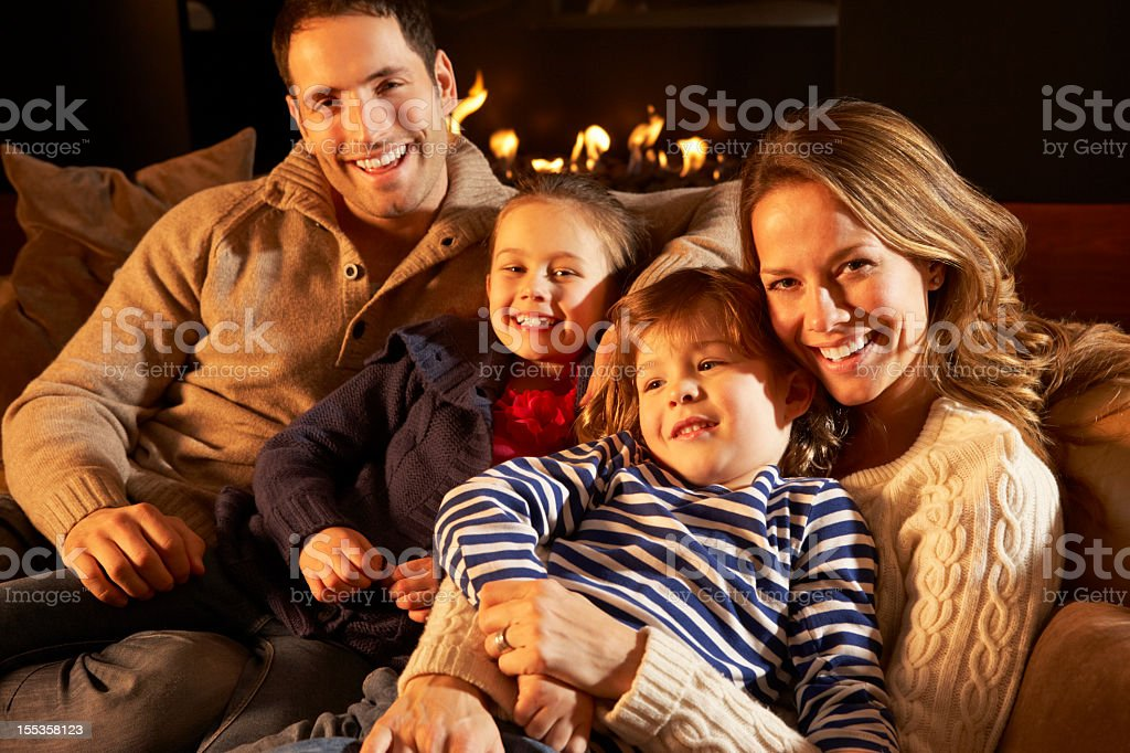 Portrait family relaxing at home by firelight royalty-free stock photo