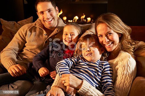 Portrait family relaxing at home by firelight smiling to camera