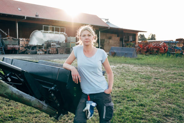 portrait: female farmer leans against a tractor, looking at camera stock photo