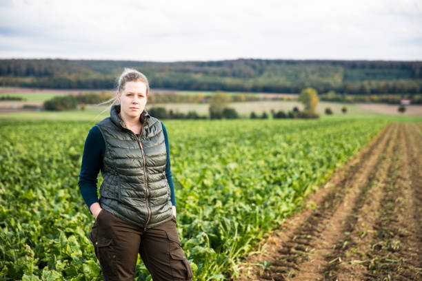 Portrait: female farmer stands in agricultural field with sugar beets stock photo