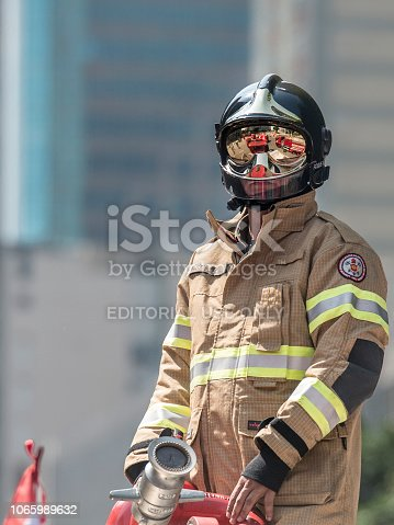 Rio de Janeiro, Rio de Janeiro, Brazil. 07th September 2016. Firefighter on top of fire truck wearing full combat suit with reflective glasses and helmet. Rio de Janeiro downtown emergency services.