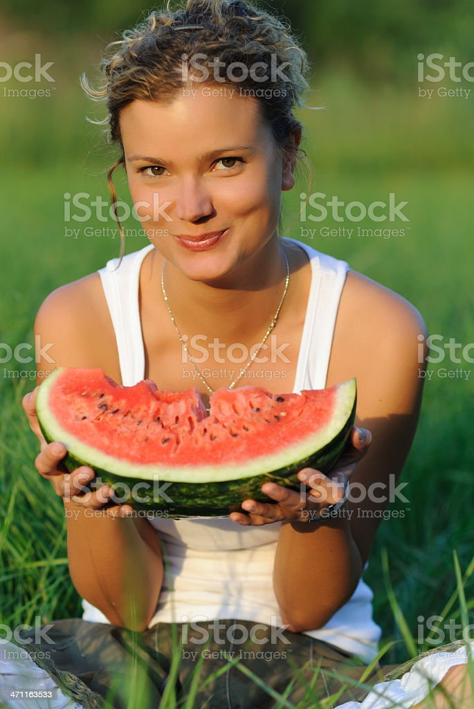 Portrait from a young woman eating watermelon in green grass royalty-free stock photo